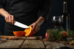 Close-up view of chef cuts fresh orange on wooden board fore preparing mulled wine on rustic wooden table with festive composition background. Backstage of cooking hot drink with fragrant spices