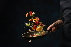 Close-up view of chef's hand throws up frying mix of colored vegetables above the pan on dark blue background. Backstage of cooking meal. Frozen motion. Food banner concept.