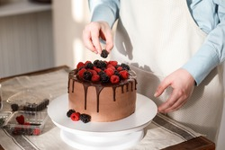 Close up view of chocolate cake decorating process. Woman is decorating homemade cake with berries, raspberries and blackberries. Delicious dessert for birthday or wedding.