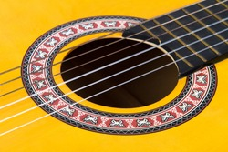 Close up view of classical guitar includes with strings, fingerboard and part of body.