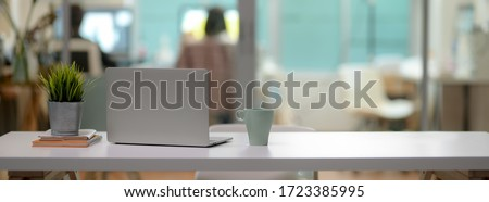 Close up view of comfortable office desk with laptop, mug, tree pot, office supplies and copy space on white table in glass partition office