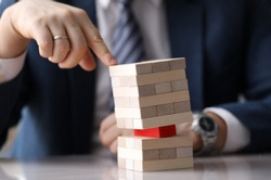 Close-up view of company leader pressing on wooden tower on one hand. Skewed pyramid of light blocks with one red brick in the middle. Risk and vulnerable situation concept