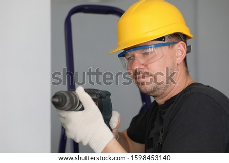 Close-up view of concentrated construction workers face drilling hole in wall. Professional builder holding perforator equipment in hand. Foreman concept