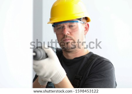 Close-up view of concentrated male drilling hole in wall. Professional builder wearing yellow protective helmet and eyewear. Construction and foreman concept