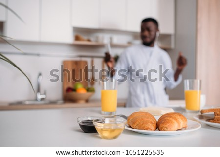 Close up view of croissants on plate, orange juice, jams and butter with young man in earphones on blurred background #1051225535