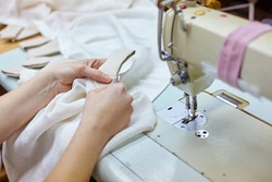 Close up view of cropped female hands sewing white fabric on professional manufacturing machine at seamstress workplace. Tailor hands holding textile sewing item. Soft focus