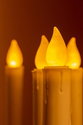 Close up view of defocused flameless candlesticks with golden color bases, illuminating a darkened room with an attractive amber glow