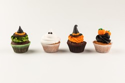 close-up view of delicious spooky halloween cupcakes isolated on white