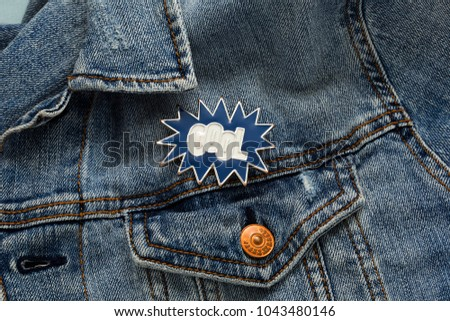 Close up view of denim jacket with cool cartoon graphic pin message, funky metallic brooch fashion accessory #1043480146