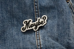 Close up view of denim jacket with graphic pin, funky metallic fashion accessory