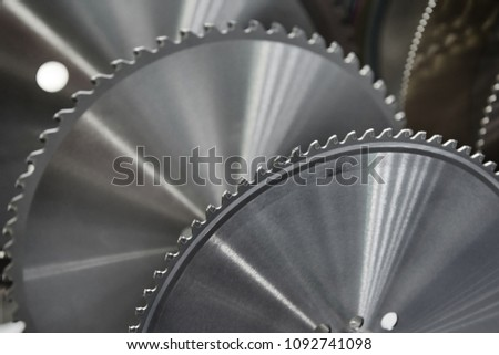 Close up view of disc saw in the main focus and many disc saws of different types in the background. Disk saw cutting tools for wood and metal treatment machinery undustry