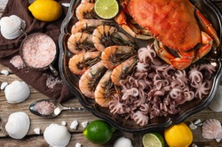 Close-up view of dish with assorted seafood. Cooked crab, baby octopuses and tiger shrimps served with ice cubes, lime and seashells on rustic wooden background. Seafood concept. View from above.