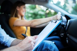 Close up view of driving instructor holding checklist while in background female student steering and driving car. Acquiring driver's license.