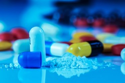 Close Up view of drug powder of antibiotics contain blue pills, yellow-red or capsules on a white background with copied clearance. Medication in healthy containers, antibiotics and dangerous drugs.