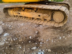Close up view of excavator tracks in a construction site.