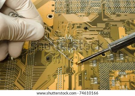 close up view of expert in white mitten is repairing circuit board using soldering iron and solder