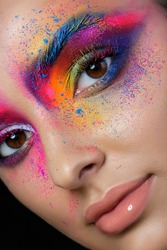 Close up view of female face with bright multicolored fashion makeup. Holi indian color festival inspired. Studio macro shot