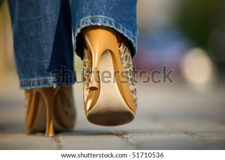 Close-up view of female in jaguar spotted shoes walking outdoors