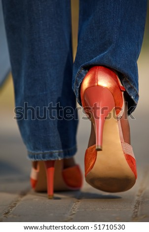 Close-up view of female in red shoes walking outdoors