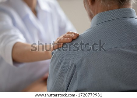 Close up view of female professional doctor, nurse or caregiver hand touching shoulder of senior elder old male patient expressing trust, support. Elderly people medical health care, medicare concept.