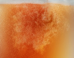 Close up view of floating bubbles in golden colored beer background. Texture of cooling summer's unfiltered drink with foam and macro fizz on the glass wall. Fizzing or floating up to top of surface.