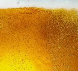 Close up view of floating bubbles in light golden colored beer background. Texture of cooling summer's filtered drink with foam and macro fizz on the glass wall. Fizzing or floating up to top of