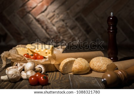 close up view of fresh cherry tomatoes, cheese, mushrooms and loafs of bread on baking paper on wooden tabletop #1088321780