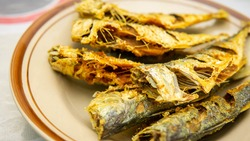 Close up view of fried mackerel fish serve in a plate on a table background. Traditional Malaysia served food for lunch.
