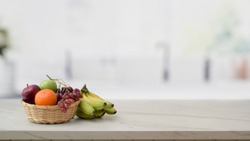 Close up view of fruit basket and copy space on marble desk with blurred kitchen room background