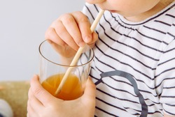 Close up view of girl child party drinking mixed juice with natural biodegradable bamboo straw. Plastic free lifestyle concept.