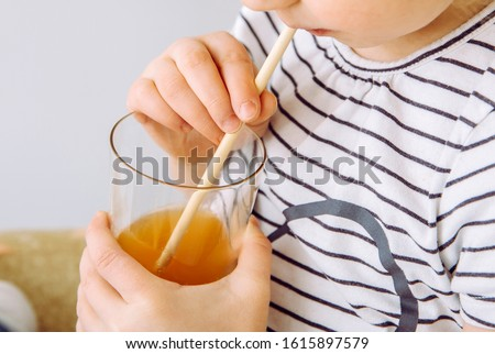 Close up view of girl child party drinking mixed juice with natural biodegradable bamboo straw. Plastic free lifestyle concept.  Stock photo ©