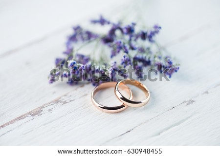 Close-up view of golden wedding rings and beautiful small blue flowers on wooden tabletop Stock photo ©