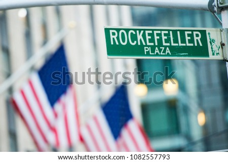 Close-up view of green street sign depicting it is Rockefeller Plaza in Midtown Manhattan, New-York. Blurred American flags in the background
