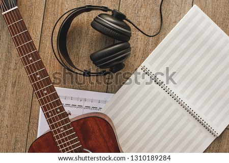 Close up view of guitar, professional headphones and musical notes laying on the wooden floor. Musical instruments. Music equipment