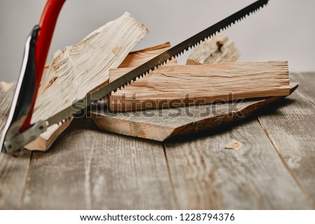 Close up view of hacksaw and wood logs on wooden table on grey background