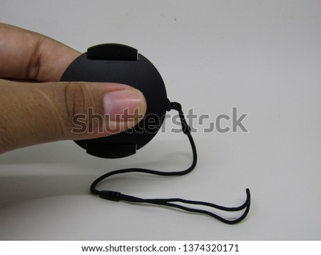 Close up view of hand holding black lens cap camera prosumer dslr with strap isolated on white background. Side view equipment  professional concept