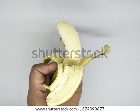 Close up view of  hand holding Peeling into four side peels off one yellow banana peel isolated on white background. Organic local tropical fruit healthy for daily consume brown spots on the skin.  #1374390677