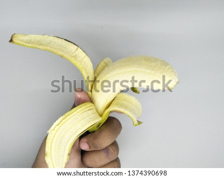 Close up view of  hand holding Peeling into four side peels off one yellow banana peel isolated on white background. Organic local tropical fruit healthy for daily consume brown spots on the skin.  #1374390698