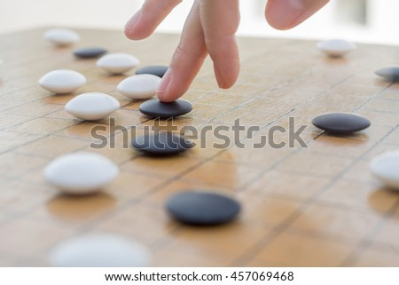 Close up view of hand playing black and white stone pieces on Chinese go game board.  ストックフォト ©