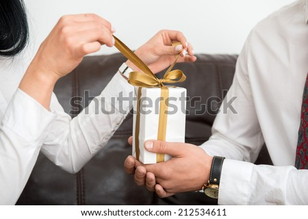Close-up  view of hands of man giving white gift box, female hands opening gift box in office interior