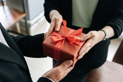 Close-up view of hands of unrecognizable woman giving red gift box tied to bow handed to man. Giving gifts during the Christmas, Happy New Year and Happy Birthday at office.