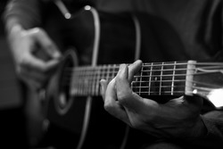Close up view of hands playing acoustic western guitar. Black and white image.
