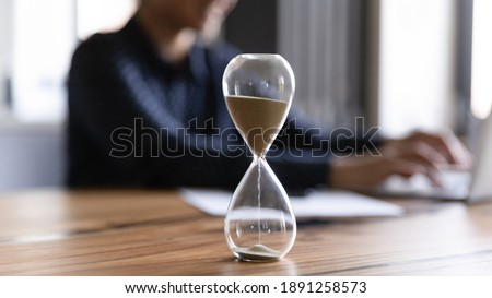 Close up view of hourglass stand on wooden home office measuring time, woman busy using computer. Female employee on background work on laptop, try to meet deadline. Efficiency concept.