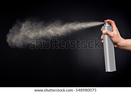 Close-up view of human hand and spray bottle isolated on black #548980075