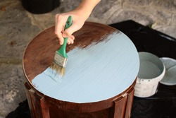 Close up view of human hand painting furniture - Image
