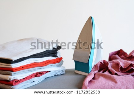 Close up view of iron clothes on ironing board with stack of ironed shirts. Housework concept #1172832538