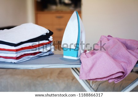 Close up view of iron clothes on ironing board with stack of ironed shirts. Housework concept #1188866317
