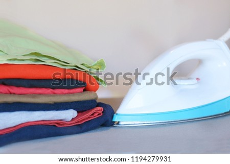 Close up view of iron clothes on ironing board with stack of ironed shirts. Housework concept #1194279931