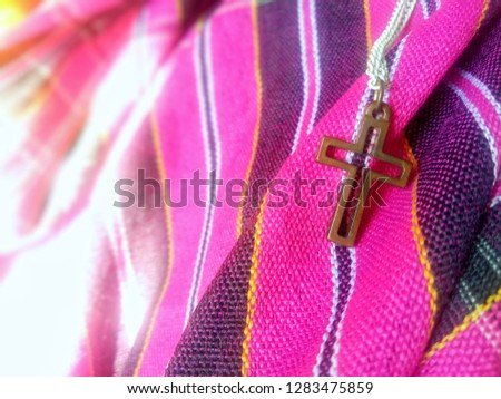 Close up view of Jesus christian crucifix cross on colorful local cloth, God loving concept picture with selective focus
