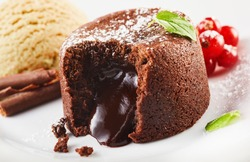 Close up view of lava cake filled with chocolate against ice cream and berries